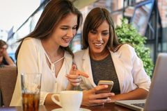 Two young girls sitting in cafe using smart phone. Girl showing her friend something on phone Royalty Free Stock Image