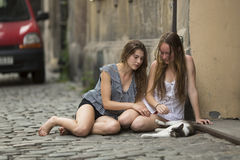 Two young girls sitting with a cat on the pavement. Stock Photography