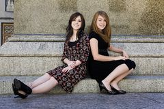 Two young girls sitting downtown Stock Image