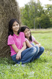 Two young girls sitting by haybale Royalty Free Stock Images