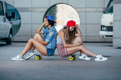 Two young girls sitting on longboard. And looking to smartphone Stock Images