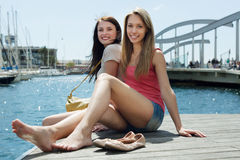 Two young girls sitting near the bridge on the sea Royalty Free Stock Photos