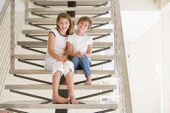 Two Young Girls Sitting On A Staircase At Home Stock Image