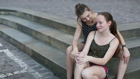 Two young girls sitting on the stone steps, spend time talking.