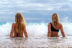 Two young girls sitting in the surf. With big waves and greay sky with clouds Royalty Free Stock Photo