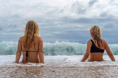 Two young girls sitting in the surf. With big waves and greay sky with clouds Stock Photo