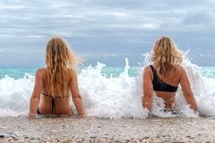 Two young girls sitting in the surf. With big waves and greay sky with clouds Stock Photography