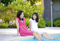 Two young girls sitting by swimming pool, smiling. Two young girls, biracial, part- Asian, enjoying time sitting by pool Royalty Free Stock Photo