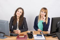 Two young girls sitting at a table in the office and looking at the frame. Two young pretty business women sitting at a office table is divided into two jobs royalty free stock photo