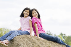 Two young girls sitting on top of haybale Stock Photography