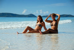 Two young girls sitting in water at beach. Two sexy young girls sitting in the water at paradise beach with mountains in background Royalty Free Stock Image