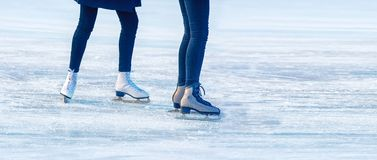Two young girls are skating on the rink. Feet closeup Stock Images