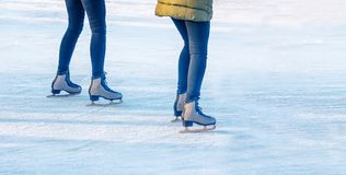 Two young girls are skating on the rink. Feet closeup Stock Photos