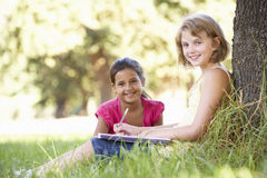Two Young Girls Sketching In Countryside Leaning Against Tree Stock Photos