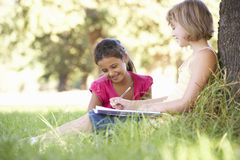 Two Young Girls Sketching In Countryside Leaning Against Tree Stock Photography