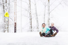 Two young girls sledding down hill in ice and snow Royalty Free Stock Images