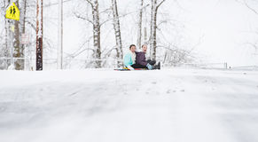 Two young girls sledding down hill in ice and snow Royalty Free Stock Image