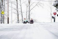 Two young girls sledding down hill in ice and snow Royalty Free Stock Photos