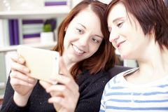 Two young girls with smart phone Stock Images