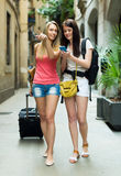 Two young girls smiling with baggage. And heading to hotel on foot stock images