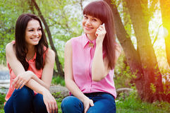 Two young girls smiling with cell phone Royalty Free Stock Photography
