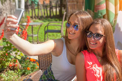 Two young girls smiling and taking selfie outdoors. Friendship and lifestyle concept. Two young and cheerful girls having fun and taking selfie in cafe at stock photo