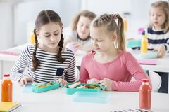 Two young girls during snack time in a school looking into each royalty free stock images