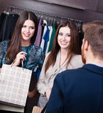 Two girls speak to shop consultant Stock Photography