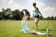 Two young girls stetching before a jogging Stock Photos