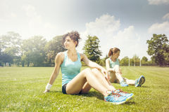 Two young girls stetching before a jogging Stock Images