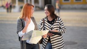 Two young girls on the streets of the old city. Girlfriends try to find their way in an unfamiliar city. Tourists. Carefully consider the map of the area stock footage