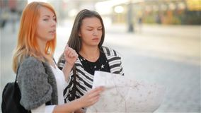 Two young girls on the streets of the old city. Girlfriends try to find their way in an unfamiliar city. Tourists. Carefully consider the map of the area stock video footage