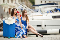 Two young girls with a suitcase on a Marina Royalty Free Stock Image