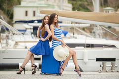 Two young girls with a suitcase on a Marina Stock Photo
