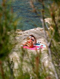 Two young girls sunbathing on rocks by the sea Royalty Free Stock Photos
