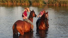 Two young girls swim with their horses in the lake. In summer, slow motion stock footage