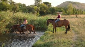 Two girls with their horses swimming in the lake. Two young girls swim with their horses in the lake in summer, slow motion. One horse goes into the water and stock video