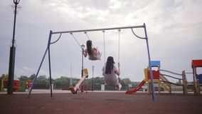 Two young girls on swings stock video footage