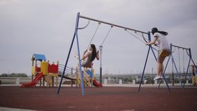 Two young girls on swings stock video