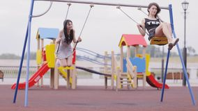 Two young girls on swings. Two young brunette women riding on swings in child`s park in early morning stock video
