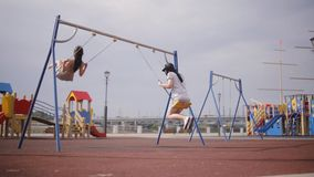 Two young girls on swings stock footage