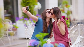 Two young girls taking selfie by smart phone at the outdoors cafe. stock video footage