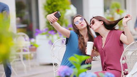Two young girls taking selfie with smart phone at the outdoors cafe. Two women after shopping with bags sitting in stock footage