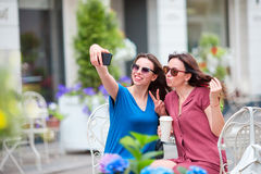 Two young girls taking selfie with smart phone at the outdoors cafe. Two women after shopping with bags sitting in stock photo