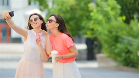 Two young girls taking selfie with smart phone outdoors. Two women after shopping with coffee using smartphone stock video footage