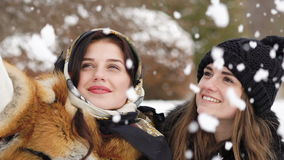 Two young girls taking selfie in winter park. Slow motion stock video footage