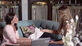 Two young girls talk on a sofa at office. The girl shows to the client the range of drapery. On this video you can see as the woman shows to the client the stock footage