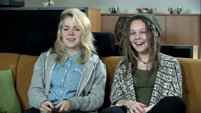 Two young girls talk to each other while watching television series. Two females talking to each other during the television show stock video