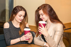 Two young girls talking in a cafeteria Stock Image