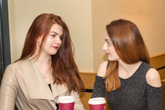 Two young girls talking in a cafeteria. Close up portrait of two young girls talking in a cafeteria and hold coffee mugs stock photo